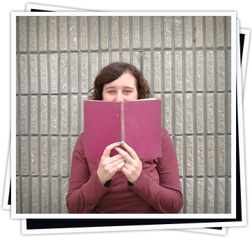 Portrait of Jennifer Rose hiding behind a book