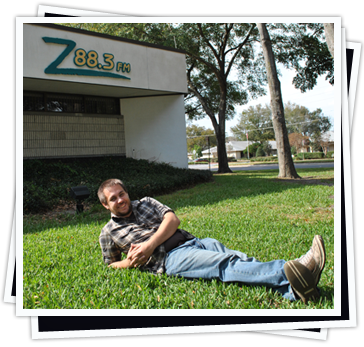 Ray Hill laying in the lawn in front of the Z88.3 Studio Office